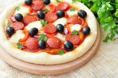Pizza fatta a mano con salame, la mozzarella, le olive, la cipolla e la salsa al pomodoro Fotografie Stock Libere da Diritti