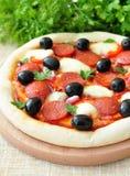 Pizza fatta a mano con salame, la mozzarella, le olive, la cipolla e la salsa al pomodoro Immagini Stock
