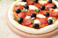 Pizza fatta a mano con salame, mozzarella, olive, cipolla Immagini Stock Libere da Diritti