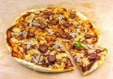 A pizza feito a mão com salame, mexilhões e cogumelos, fritou partes Foto de Stock Royalty Free