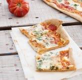 Pizza fina con el tomate, el queso rallado e hierbas Imágenes de archivo libres de regalías