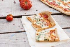Pizza fina con el tomate, el queso rallado e hierbas Imagen de archivo