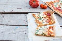 Pizza fina con el tomate, el queso rallado e hierbas Fotografía de archivo