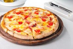 Pizza Fleisch des selektiven Fokus mit hamon, Käse- und Kirschtomaten auf dem hölzernen Brett auf der gedienten Restauranttabelle Lizenzfreie Stockfotografie