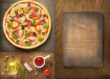 Pizza and food ingredients at wooden table royalty free stock images