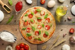 Pizza and food ingredients at wooden table royalty free stock photography