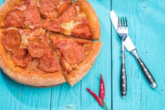 Pizza with fork and knife on a blue wooden table. Stock Photos