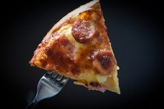 Pizza on fork / Slice pizza piece on the dark black stock photo