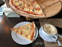 Pizza four cheese and coffee in a white mug in a cafe top view royalty free stock photography