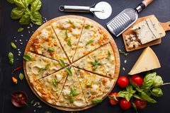 Pizza four cheeses. Delicious sliced pizza on a chalk board Royalty Free Stock Image