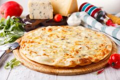 Pizza four cheeses. A whole pizza on white wooden table Stock Photos