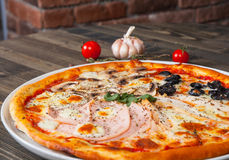 Pizza Four Seasons on a white plate Stock Photo