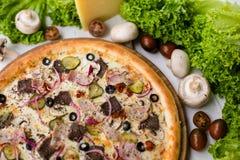Pizza fraîche délicieuse avec du boeuf, le lard, les concombres marinés, les olives et le fromage sur la table en bois blanche en photo stock