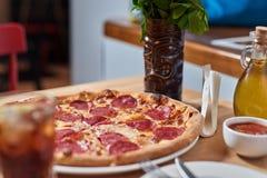 Pizza fresca com a salsicha dos pepperoni na tabela de madeira no restaurante Imagens de Stock Royalty Free