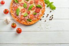 Pizza fresca con i pomodori, il formaggio ed il salame su un primo piano di legno della tavola immagine stock