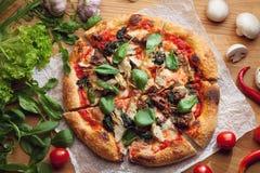 Pizza fresca con los ingredientes en la tabla de madera Imágenes de archivo libres de regalías