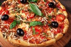 Pizza fresca con los tomates, el queso y las setas en el primer de madera de la tabla Fotos de archivo libres de regalías