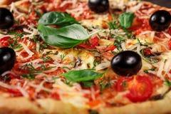 Pizza fresca con los tomates, el queso y las setas en el primer de madera de la tabla Foto de archivo