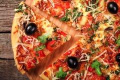 Pizza fresca con los tomates, el queso y las setas en el primer de madera de la tabla Foto de archivo libre de regalías