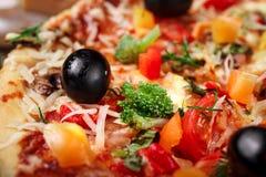 Pizza fresca con los tomates, el queso y las setas en el primer de madera de la tabla Fotografía de archivo libre de regalías