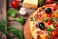 Pizza fresca con los tomates, el queso y las setas en el primer de madera de la tabla Imágenes de archivo libres de regalías