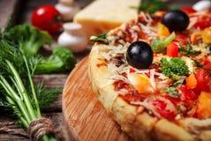 Pizza fresca con los tomates, el queso y las setas en el primer de madera de la tabla Imagen de archivo