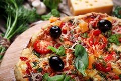 Pizza fresca con los tomates, el queso y las setas en el primer de madera de la tabla Imagen de archivo libre de regalías
