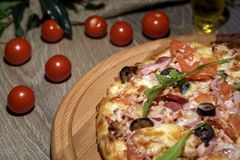 Pizza fresca deliciosa servida en la tabla de madera fotografía de archivo