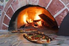 Pizza fresca fuera de un horno ardiente de madera Foto de archivo