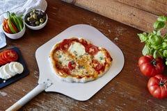Pizza fresca na pá com ingredientes Fotos de Stock