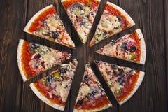 Pizza fresca saboroso cortada com cogumelos e salsicha em um fundo de madeira Imagem de Stock Royalty Free