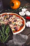 Pizza fresca saboroso cortada com cogumelos e salsicha em um fundo de madeira Imagens de Stock Royalty Free