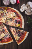 Pizza fresca saboroso cortada com cogumelos e salsicha em um fundo de madeira Fotos de Stock