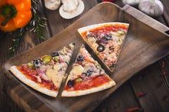Pizza fresca saboroso cortada com cogumelos e salsicha em um fundo de madeira Fotografia de Stock Royalty Free