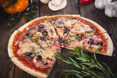 Pizza fresca saboroso cortada com cogumelos e salsicha em um fundo de madeira Foto de Stock