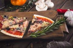 Pizza fresca saboroso cortada com cogumelos e salsicha em um fundo de madeira Foto de Stock Royalty Free