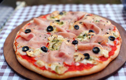 Pizza with fresh ham, mozzarella and black olives Stock Photos