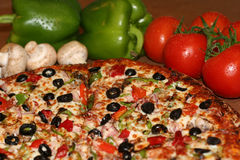 Pizza and Fresh Ingredients. Appetizing pizza with fresh vegetables on the side; mushrooms, green peppers, and tomatoes Royalty Free Stock Photography