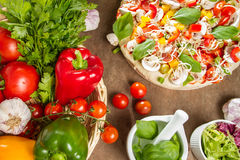 Pizza and fresh ingredients Royalty Free Stock Images