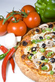 Pizza and fresh ingredients. Still-life of pizza topped with green peppers, pepperoni, black olives, mushrooms, sauce and cheese...surrounded by fresh vegetable Stock Image