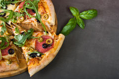 Pizza. Fresh spicy italian pizza with salami sausage and fresh rocket stock photos