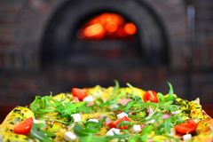 Pizza in front of a stone stove. With fire. Design material for a traditional pizzeria restaurant Stock Images