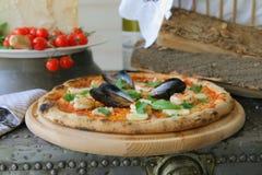 ` Pizza ` Frutti di mare mit Miesmuscheln, Muscheln und frischem Basilikum lizenzfreie stockfotografie