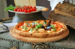 ` Pizza ` Frutti di mare mit Miesmuscheln und frischer Basilikum stockbild