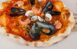 Pizza frutti di mare with shrimps, open clams and mussels and basilic Stock Image