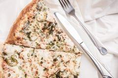 Pizza, gaffel och kniv på en platta Fotografering för Bildbyråer