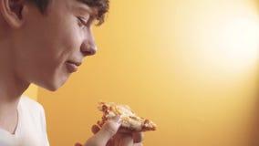 Pizza gelukkige tienerjongen die een plak van de levensstijl van het pizzaconcept eten hongerige de tiener eet een plak van pizza stock videobeelden