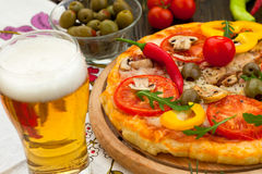Pizza with glass of beer Stock Photos