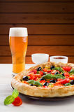 Pizza and glass of beer on the table Royalty Free Stock Images