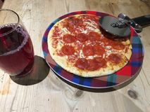 Pizza with a glass and pizza cutter royalty free stock photo